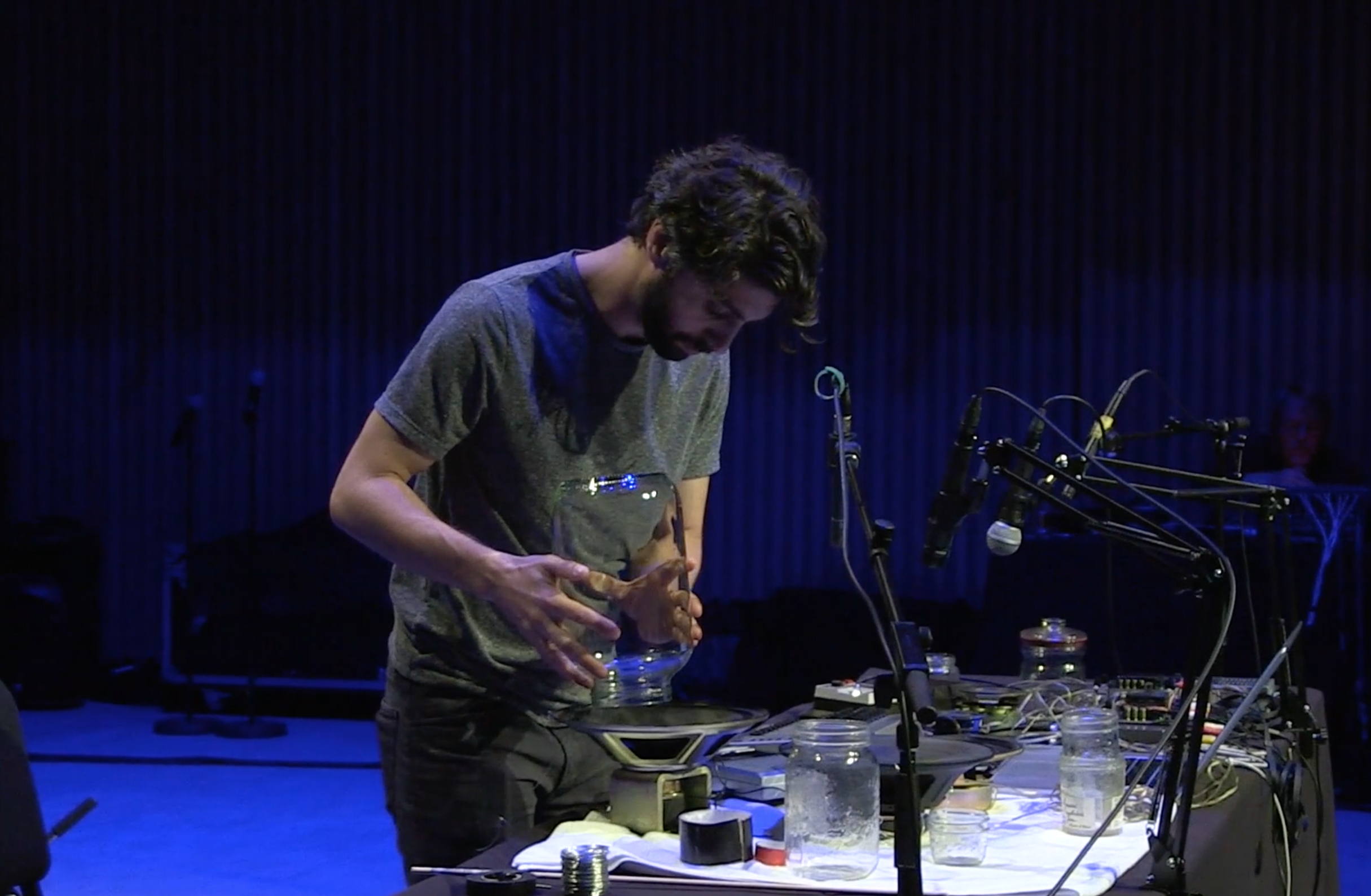 Adam Basanta uses a jar for preparing a loudspeaker.